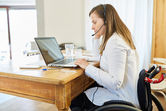 Paralyzed business woman in a wheelchair during a video conference