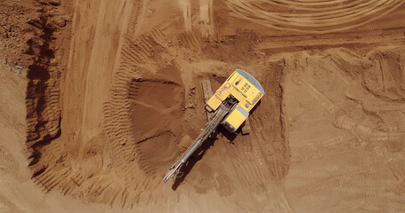 Fototapeta Aerial view of a digger, tracked excavator at work on a construction. obraz