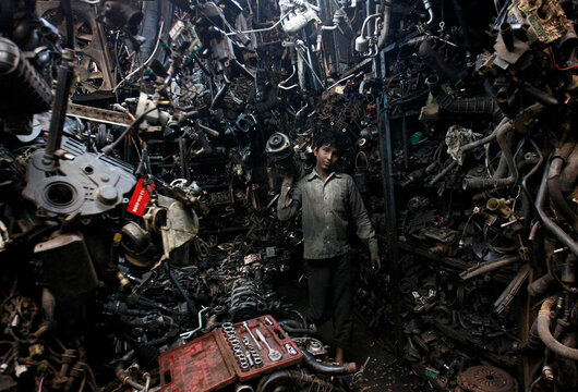 Abdul Samad carries a part of a used car engine inside an automobile workshop in Mumbai