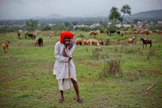 A shepherd reacts to being photographed while watching over his sheep in a pasture on the outskirts of Chakan