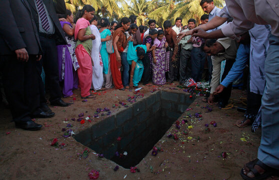 People throw flowers and soil on Jacintha Saldanha's grave during her funeral at a cemetery in Shirva