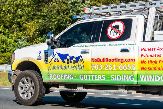 Herndon, USA - October 7, 2020: Pickup truck for small local roofing business doing roof repair work, gutters cleaning, siding and windows on residential homes in Northern Virginia with ladder at back