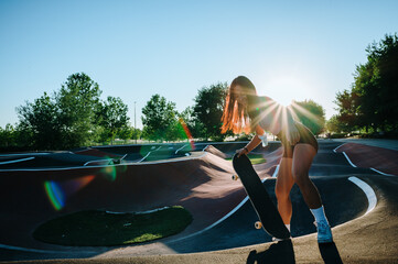 Obraz Asian skater girl having fun when she is skateboarding.  She is wearing a pink t-shirt, black pants, white socks, and white sneakers.  She is at the skatepark and as you can see the sunset is awesome! - fototapety do salonu