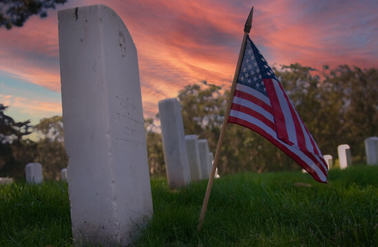 Small American Flag Rests In Front Of A Fallen Military Heros Tombstone