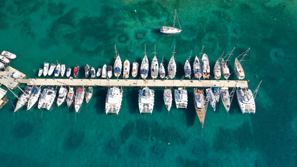 Obraz Aerial drone top down photo of exotic island marina with emerald clear sea a safe anchorage for yachts and sailboats - fototapety do salonu