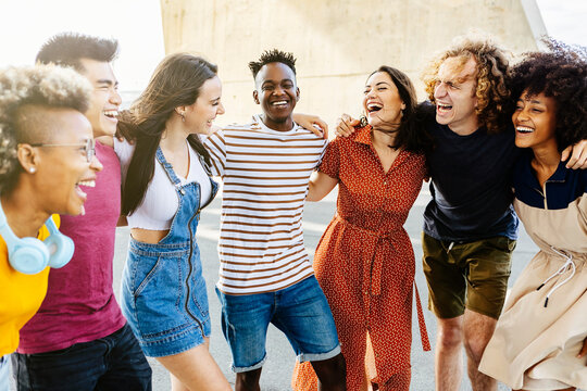 Group of happy multiracial people having fun together outdoor - Smiling young adult friends laughing and hugging each other in the street. Happiness, friendship and summer holidays concept - Focus on