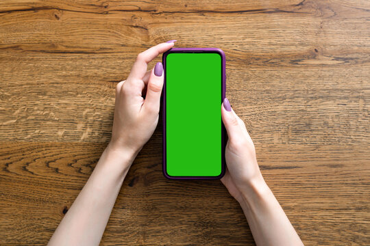 Beautiful female hands hold a smartphone on wooden background. Empty green screen for inserting your own picture or text.