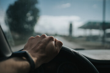 Fototapeta Drivers' hand on the steering wheel on background of the road seen through a window obraz