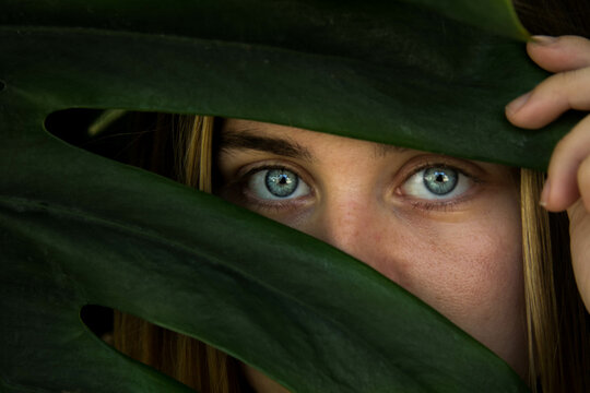 Closeup shot of a woman with blue eyes hiding behind leaves