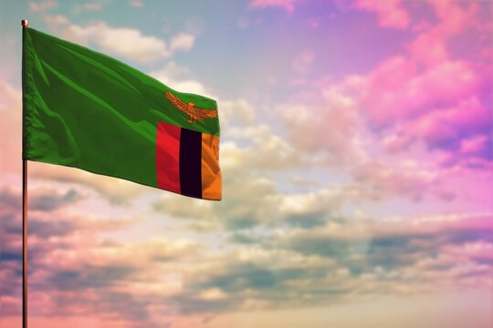 Fluttering Zambia flag mockup with the space for your content on colorful cloudy sky background.