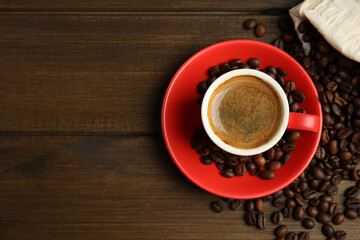 Fototapeta Cup of tasty coffee and beans on wooden table, flat lay. Space for text obraz