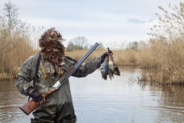 Fototapeta a hunter stands in a lake with two dead ducks in his hand obraz