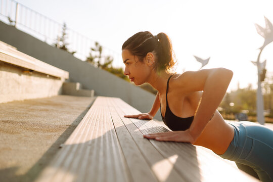 Young fitness woman exercising and stretching outdoors in the morning. Fit healthy athlete is doing workout on the street. Sport, Active life.