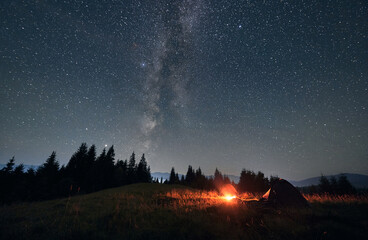 Night camping under amazing starry sky and Milky way. Wide angle view on landscape in the...