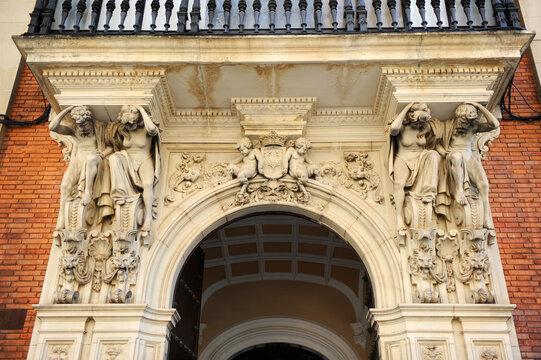 Edificio historicista en calle Reyes Católicos de Sevilla, Andalucía, España. Balcón artistico sostenido por esculturas