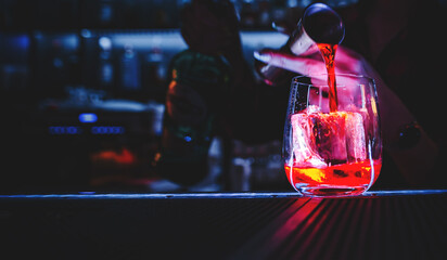 Fototapeta Closeup shot of bartender hand making negroni cocktail. Negroni classic cocktail and gin short drink with sweet vermouth, red bitter liqueur and dried orange garnish. obraz
