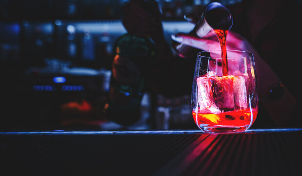 Closeup shot of bartender hand making negroni cocktail. Negroni classic cocktail and gin short drink with sweet vermouth, red bitter liqueur and dried orange garnish.