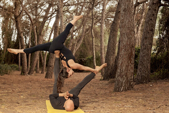 latin guy and caucasian girl doing acroyoga in the forest