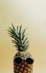 Close up shot of a pineapple with a pair of sunglasses over a pastel yellow background, copy space,...