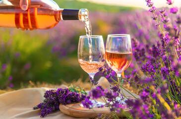 Fototapeta A woman holds wine in glasses. Picnic in the lavender field. Selective focus. obraz