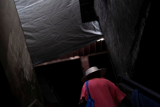 An elderly woman wearing a straw hat walks up a stair at a fresh market in Port-au-Prince