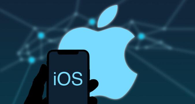 Person hält iPhone mit iOS Schriftzug in der Hand, dahinter das Apple Logo, mobile Betriebssysteme
