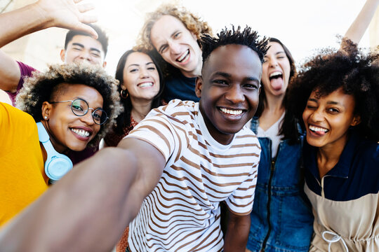 Group of multiracial happy best friends taking selfie photo with smartphone camera - Cheerful young hipster people from different cultures and races having fun together outdoor - Friendship, student