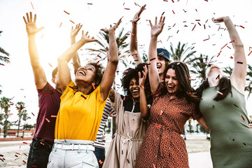 Fototapeta Group of friends enjoying party throwing confetti in the air - Multicultural young students having fun celebrating and laughing out loud outdoor - Youth, friendship and summertime concept obraz