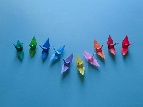 中央で下降線から上昇線を描くカラフルな折り鶴のグループ