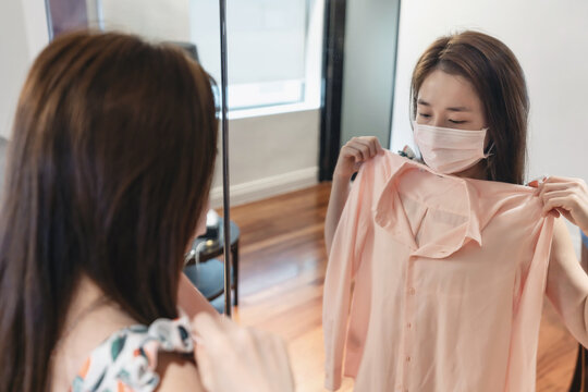 Asian woman with protective face mask, choosing and, try on clothes on the mirror