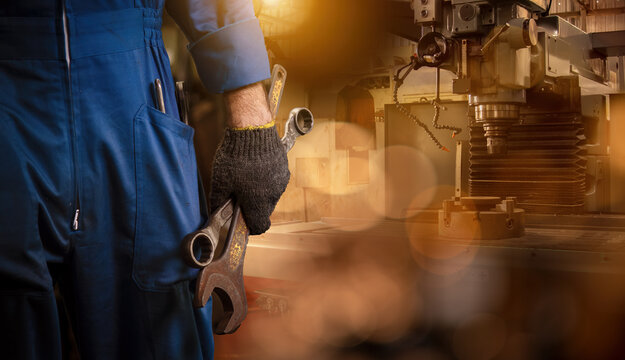 Industry engineering wear safety uniform and glove hold wrench standing on control operating machine work in industry factory with bokeh and factory station background