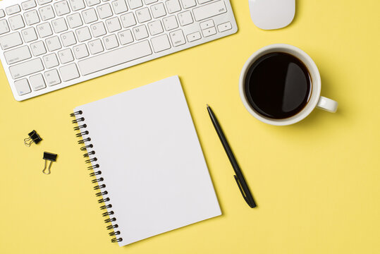 Top view photo of workplace white keyboard mouse open spiral notebook cup of coffee binder clips and pen on isolated light yellow background with blank space