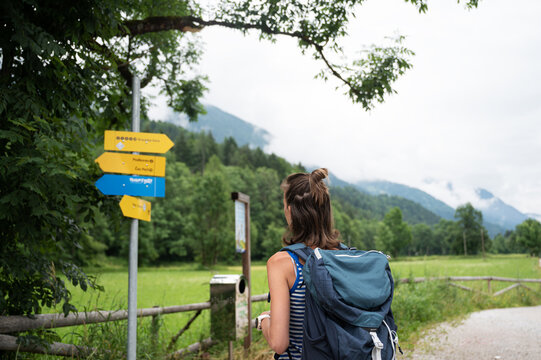 Young hiker looking at a signpost