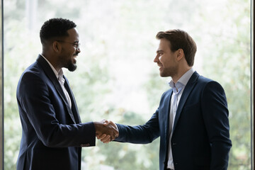 Two diverse businessmen, business partners shaking hands at window glass background. Investor and...