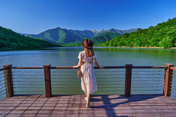Fototapeta Traveler girl standing alone on edge of pier and staring at lake and mountains. Enjoying beautiful freedom moment life and serene quiet peaceful atmosphere in nature. Back view obraz