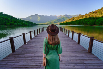 Fototapeta Traveler girl standing alone on pier and staring at lake and mountains. Beautiful freedom moment and serene peaceful atmosphere in nature. Back view obraz