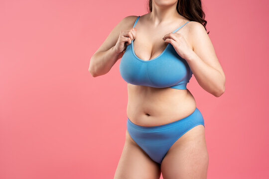 Fat woman with very large breasts in blue underwear on pink background, body care concept