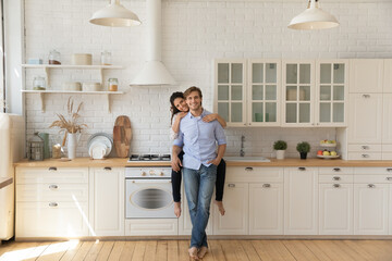 Portrait of affectionate young wife sitting on kitchen counter hug smiling husband from behind at...