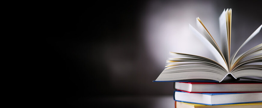 Hardcover book lying on a stack of other books