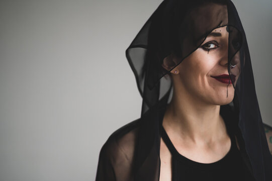 Redhead woman with a black veil on her head in a dark studio. A girl with an earring in her nose smiles slyly. Witch Makeup. Halloween costume.