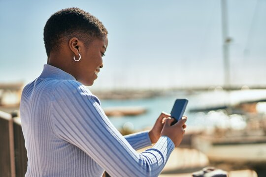 Young african american woman smiling happy using smartphone at the port