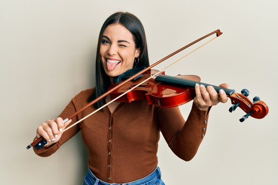 Young brunette woman playing violin sticking tongue out happy with funny expression.
