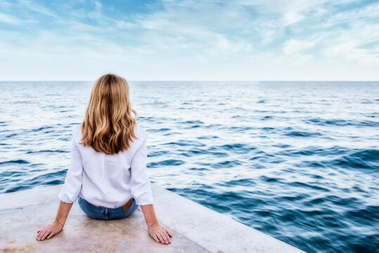 Rear view shot of a woman wearing white shirt and casual clothes while sitting on seaside and looking at the sea.