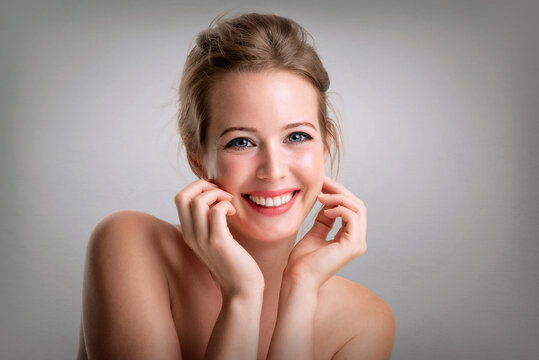 Close-up beauty portrait of gorgeous woman wearing perfect makeup while looking at camera and smiling