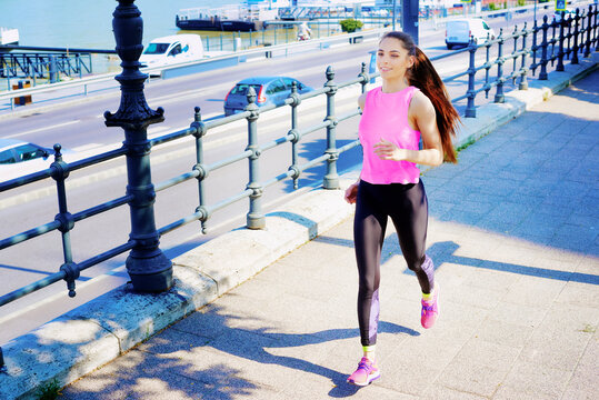 Full length shot of young woman wearing sportwear while running in the city.