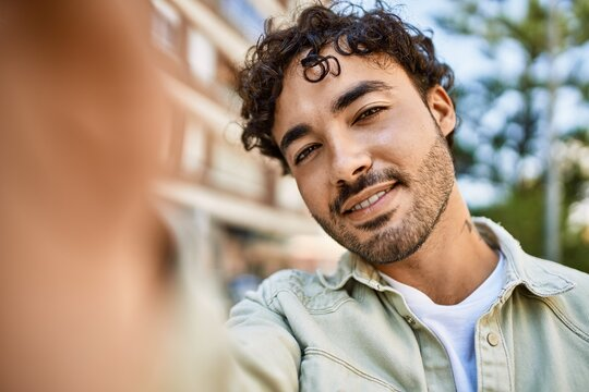 Handsome hispanic man with beard smiling happy outdoors on a sunny day taking a selfie photo