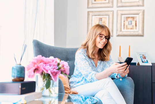 Middle aged woman using her mobile phone and text messaging at home while relaxing in armchair