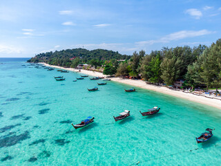 Fototapeta Aerial view of Long tail boats floating on the beautiful transparent sea at Ko Lipe in Thailand, Top view from drone obraz