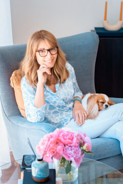 Shot of a happy middle aged woman with her cute puppy relaxing in the armchair at home