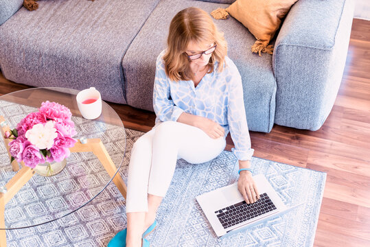 Confident woman using her laptop while sitting in the living room at home